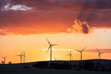 Wind Turbines Silhouetted Against Orange Sunset