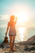 Summer Vacation. Smelling Caucasian Women Relaxing And Playing On Ukulele On Beach, So Happy And Luxury In Holiday Summer, Outdoors Sunset Sky Background. Travel And Lifestyle Concept.