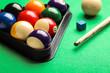 Leinwandbild Motiv Billiard balls in triangle rack, cue and chalk on green table, closeup