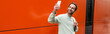 Leinwandbild Motiv cheerful man in sweatshirt taking selfie on smartphone near orange wall, banner.