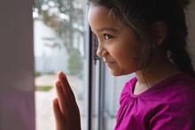 Happy Hispanic Girl Standing At Window With Hand On Glass, Looking Out And Smiling