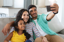 Smiling Hispanic Mother, Father And Daughter Sitting On Couch Taking Selfie Together
