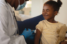 African American Female Doctor In Face Mask Giving Covid Vaccination To Scared Girl Patient At Home