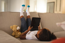 Happy African American Girl Upside Down On Couch Using Tablet, Copy Space On Screen, With Teddy Bear