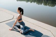 Peaceful Brunette Doing Yoga In A Scenic Beautiful Spot On A Riverside
