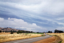 Storm Clouds Over Farming Land And Road