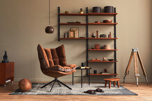 Stylish Interior Of Living Room With Design Brown Armchair, Wooden Bookcase, Pendant Lamp, Carpet Decor, Picture Frames And Elegant Personal Accessories In Modern Retro Home Decor. Template.