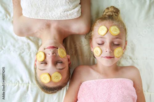 Fototapeta Beautiful girsl with facial mask of bananas. Top view.
