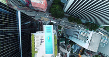 AERIAL. Top View Of Hong Kong Streets From The Drone. And Woman At The Sweeming Pool.