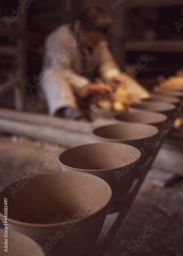 Fotografia Vertical shot of production line of ceramic bowls and a craftsman in the worksho