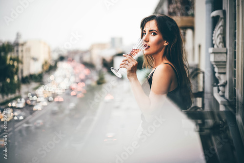 Young woman in evening dress holding champagne glass at the balcony Fototapet