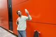 Leinwandbild Motiv cheerful man in sweatshirt taking selfie on smartphone near orange wall and longboard.