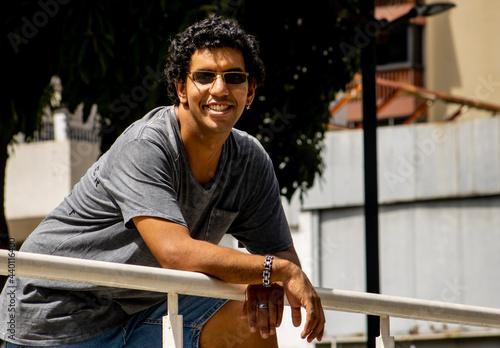 Fotografiet Smiling hispanic man leaning on the handrail outdoors