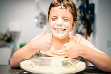 Smiling Girl Showing Thumbs Up While Face Smeared With Flour And Water