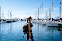 Thoughtful Female Athlete With In-ear Headphones Walking By Harbor