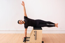 Determined Man Lying Sideways With Arm Raised On Pilates Chair In Exercise Room