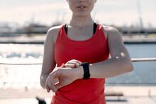 Female Jogger Checking Fitness Progress On Smart Watch