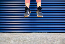 Sportswoman In Mid-air Over Footpath