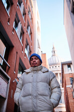 Man Walking With Hands In Pockets Of Padded Jacket With St. Paul Cathedral In Background
