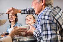 Multi-generation Family Sharing Food With Each Other At Home