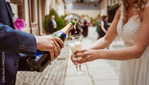 Canvas Wedding. The bride and groom pour champagne into crystal glasses