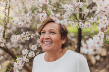 Smiling Woman Standing By Blossoming Tree