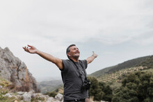 Carefree Man Standing With Arms Outstretched On Mountain