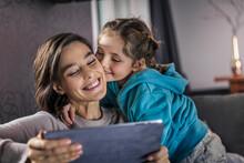 Girl Kissing Woman Using Digital Tablet In Living Room