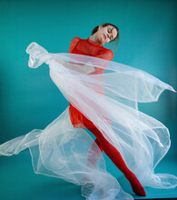 Young Female Dancer With White Tulle Net Dancing Against Turquoise Background