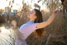 Beautiful Young Woman With Arms Raised Dancing In Nature