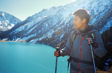 Happy Woman Wearing Backpack And Holding Hiking Poles Next To The Mountain Lake