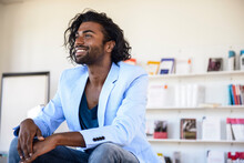 Smiling Man Looking Away While Sitting In Library