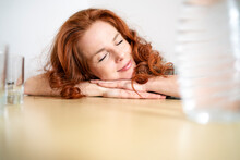 Redhead Woman Sleeping While Leaning On Table At Home