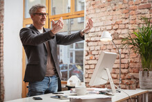 Mature Businessman Gesturing While Standing By Desk At Work Place