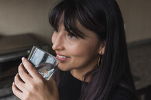 Woman Smiling While Drinking Water At Home