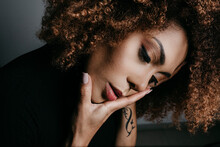 Curly Haired Woman With Head In Hands Looking Down