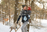 Father with sled holding son while walking in snow during winter
