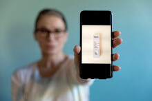 Woman Showing Photograph Of Corona Rapid Test Kit On Mobile Phone