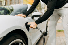 Man Plugging Electric Charger In Car At Station