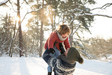 Playful Father Picking Up Son During Winter