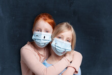 Sisters Embracing While Wearing Protective Face Mask