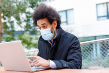 Afro Businessman Wearing Face Mask Working On Laptop During COVID-19