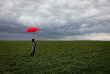 Carefree Woman With Red Umbrella Standing In Agricultural Field During Stormy Weather