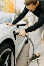 Man Plugging Electric Cord In Car At Charging Station