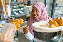 Happy Woman Buying Pastry In Bakery