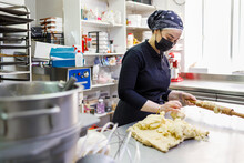 Female Baker With Rolling Pin And Dough In Commercial Kitchen At Bakery