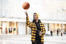 Young Man Spinning Basketball On Finger