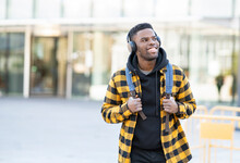 Cheerful Man Wearing Checked Yellow Jacket Listening Music Through Headphones
