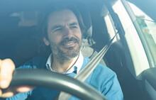 Mature Male Entrepreneur Smiling While Driving Car
