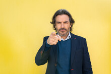 Mature Entrepreneur Pointing While Standing In Front Of Yellow Wall